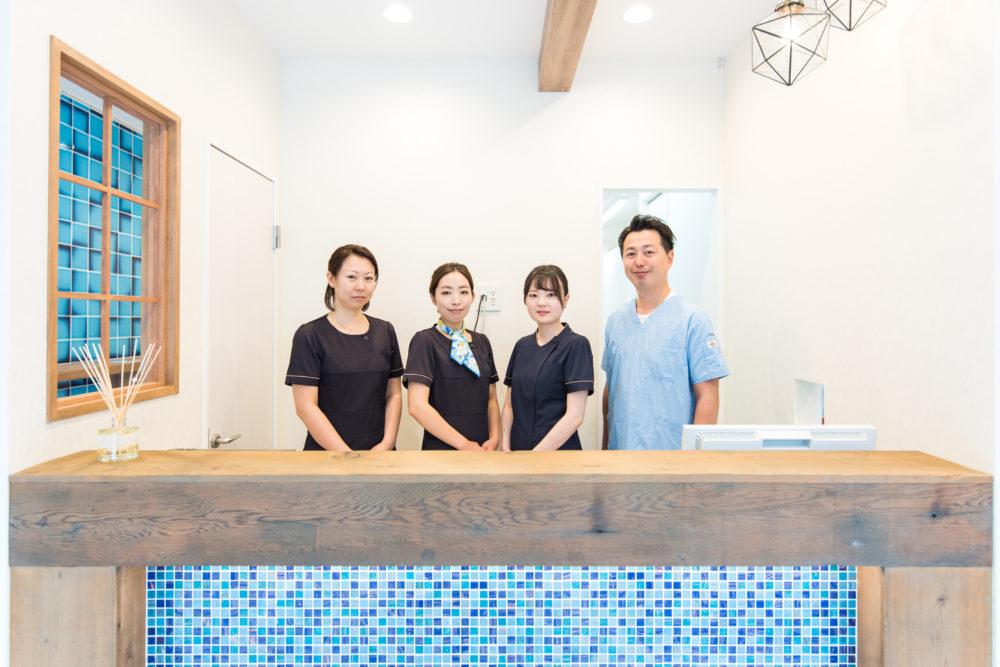 目白マリア歯科のスタッフを受付カウンタ―での笑顔の写真