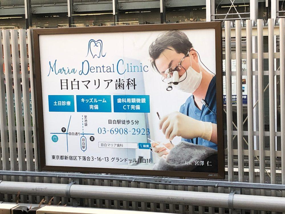 JR山手線目白駅池袋方面行ホームに設置された目白マリア歯科の看板の画像