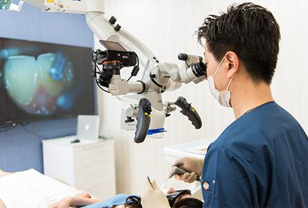 マイクロスコープを覗き精密根管治療をする東京目白のマリア歯科院長